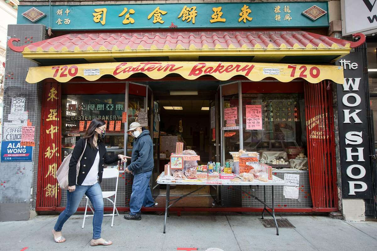A customer points at items she wants to buy while owner Orlando Kuan looks on at Eastern Bakery in Chinatown in San Francisco on Oct. 7, 2020.