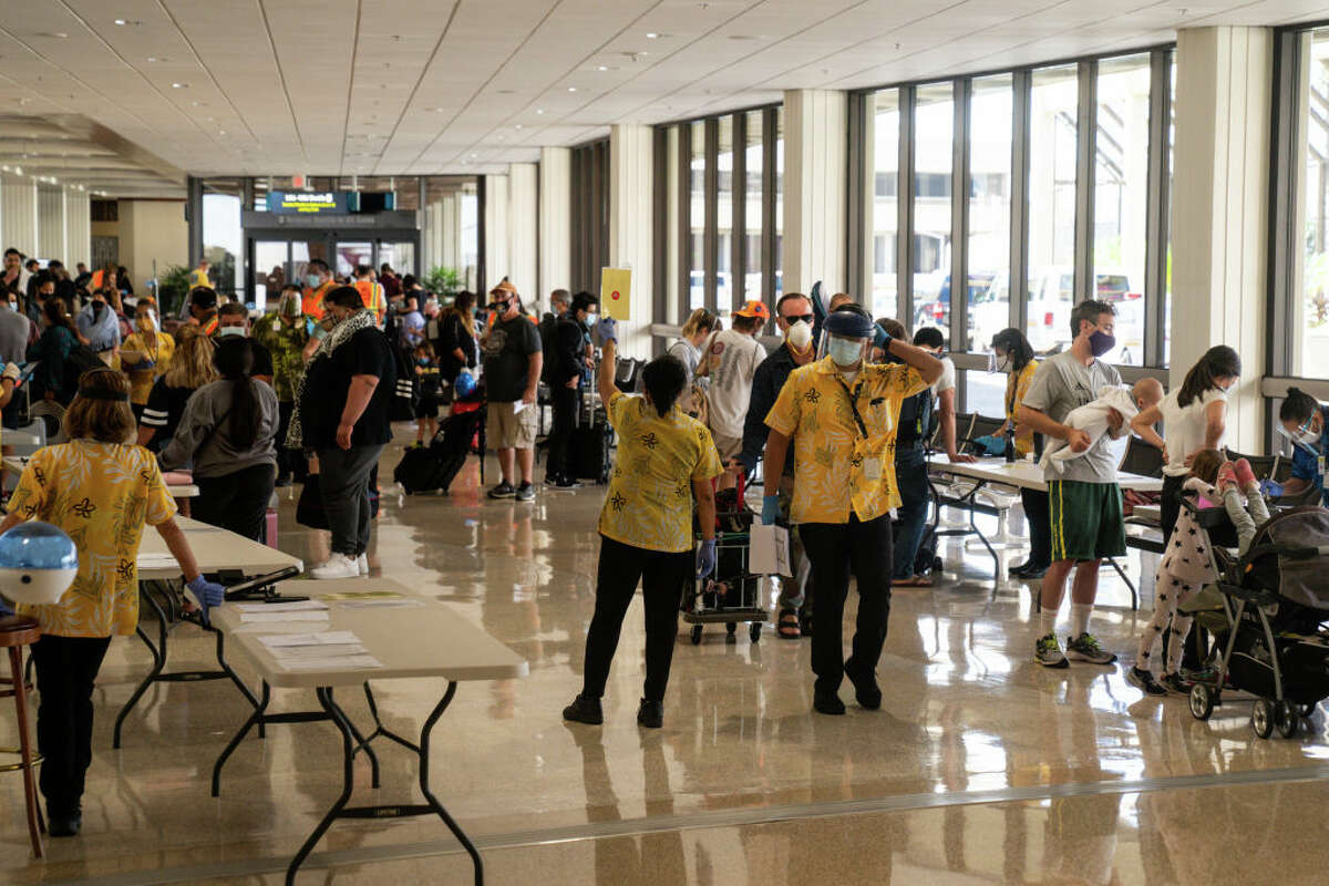 State officials check to be sure all arriving visitors and residents alike have answered a health questionnaire, had their temperatures taken and shown proof of a negative COVID-19 test at Honolulu International Airport.