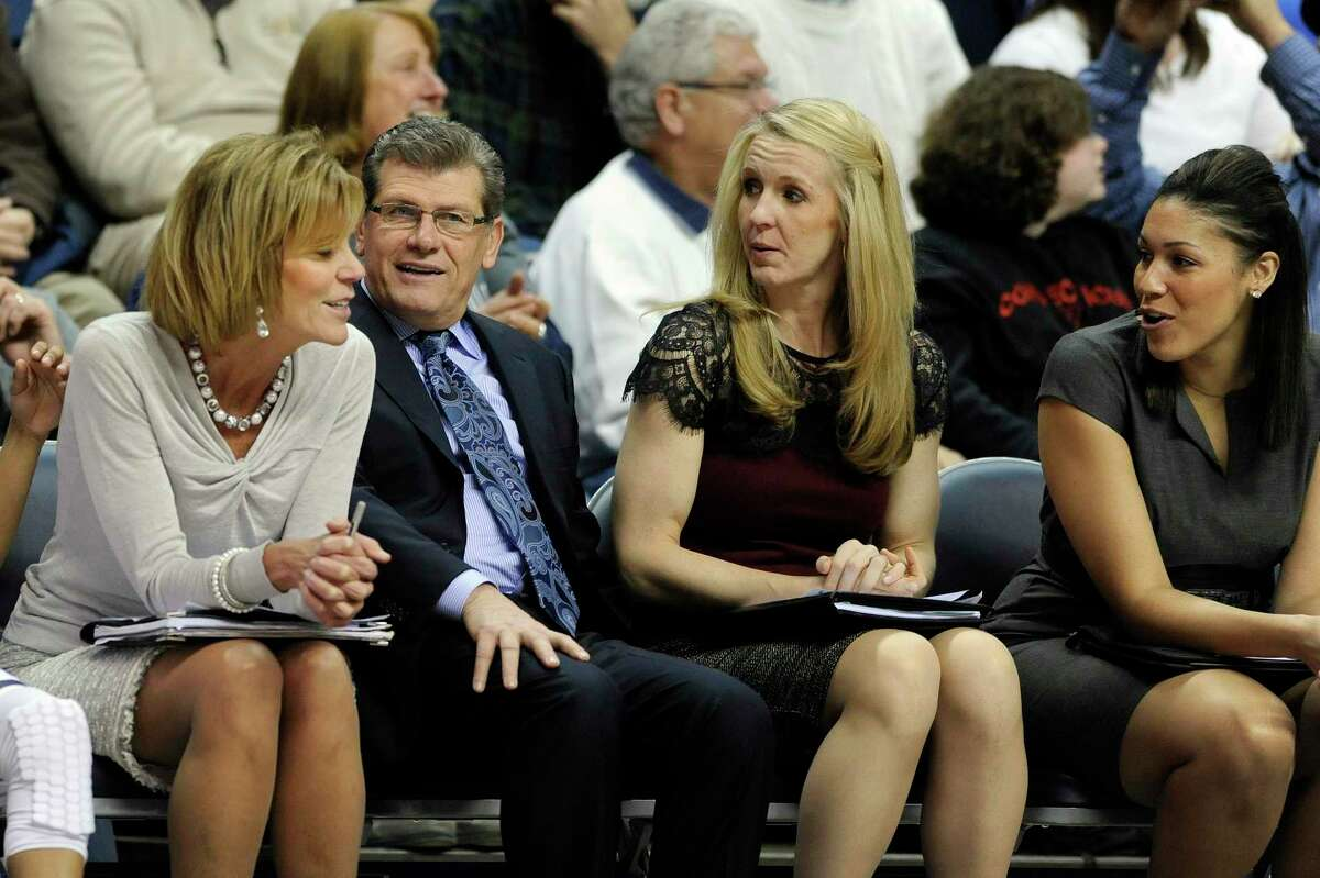 UConn coach Geno Auriemma shares a light moment with his bench with associate head basketball coach Chris Dailey, left, and assistant coaches Shea Ralph, second from right, and Marisa Moseley in 2014. UConn has agreed to pay a total of just under $250,000 to seven women, including four members of Auriemma's 2014 staff, after the U.S. Labor Department found they had been underpaid when compared with men in similar positions.