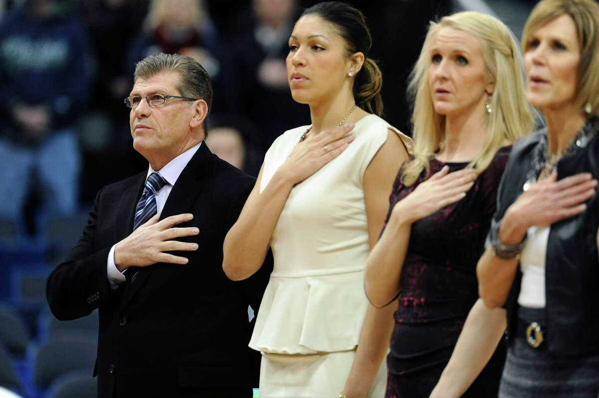 UConn coach Geno Auriemma, left, stands with assistant coaches Marisa Moseley, second from left, and Shea Ralph and associate head coach Chris Dailey, right, during the national anthem before a 2015 game. UConn has agreed to pay a total of just under $250,000 to seven women, including four members of Auriemma's 2014 staff, after the U.S. Labor Department found they had been underpaid when compared with men in similar positions.