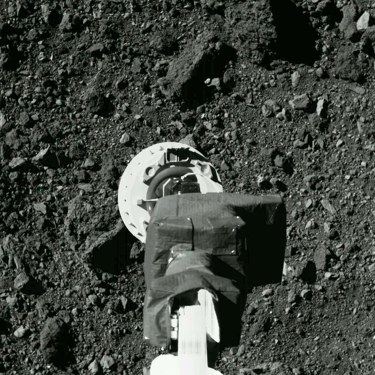 """This Aug. 11, 2020 photo shows the sampling arm of the OSIRIS-REx spacecraft during a rehearsal for an approach to the """"Nightingale"""" sample site on the surface of the asteroid Bennu. After almost two years circling the ancient asteroid, OSIRIS-REx will attempt to descend to the treacherous, boulder-packed surface and snatch a handful of rubble on Tuesday, Oct. 20, 2020. (NASA/Goddard/University of Arizona via AP)"""