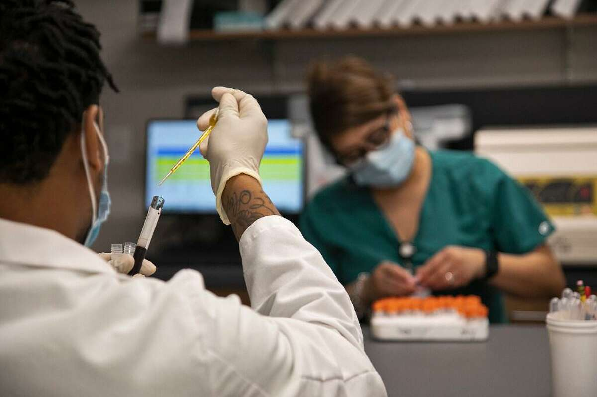 Lab technicians D'Andre White and Melinda Axton work in the laboratory at Clinical Trials of Texas, Inc. in San Antonio on Wednesday, July 29, 2020, the day before clinical trials for a COVID-19 vaccine began there.