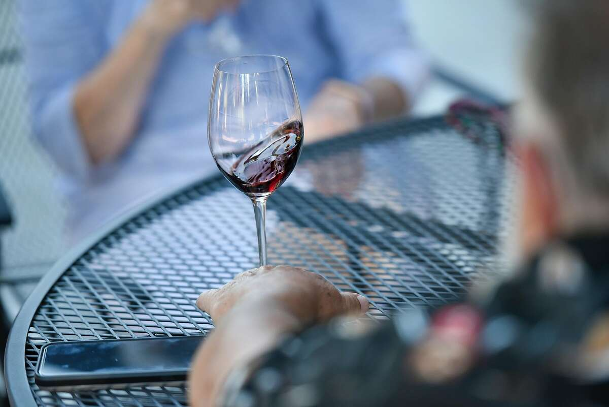 A wine is swirled by a guest on the patio at Horse & Plow Winery in Sebastopol, Calif., on Friday June 1, 2018.