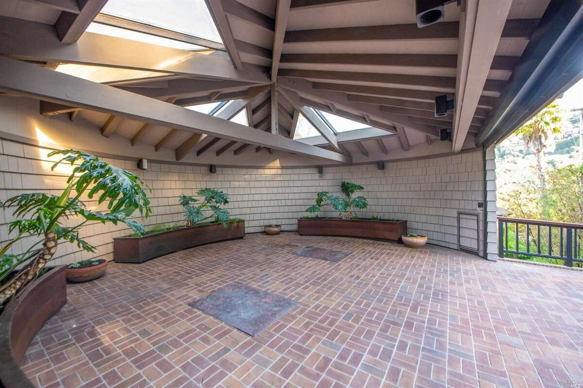 The home has a garage under the pool, but part of it is dedicated to housing the pool equipment. This circular carport was added in the mid-1980s.It has a brick floor, custom-made curved planters and a retractable electric screen door.