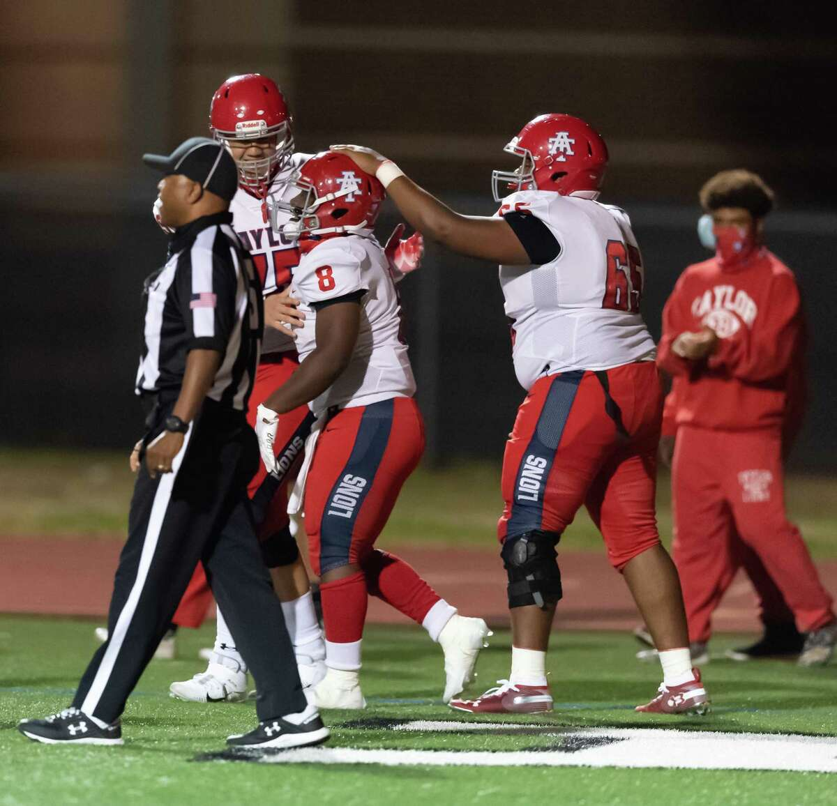 Jourdan Concepcion (8) of the Alief Taylor Lions celebrates his touchdown in the second half with his teammates against the Alief Elsik Rams during a High School football game on Friday, October 16, 2020 at Crump Stadium in Houston Texas.