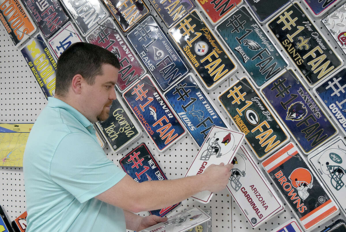 Ben McCurley, employee of The Sports Zone, stocks some sports merchandise featuring a variety of teams.