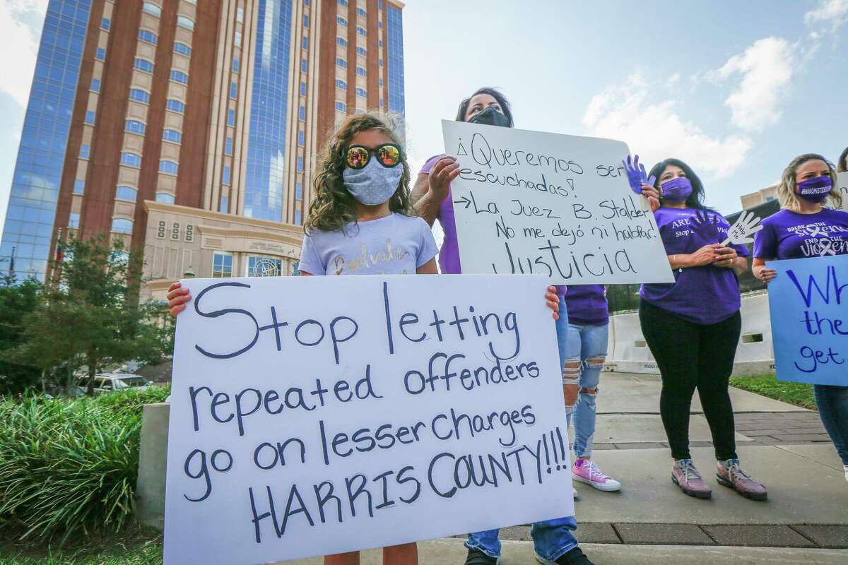 A daughter and her mother, who asked to not be identified, stand in with signs and others during a FIEL press conference to denounce inconsistencies in the way domestic violence cases are handled by law enforcement and the court system Tuesday, Oct. 20, 2020, in downtown Houston.