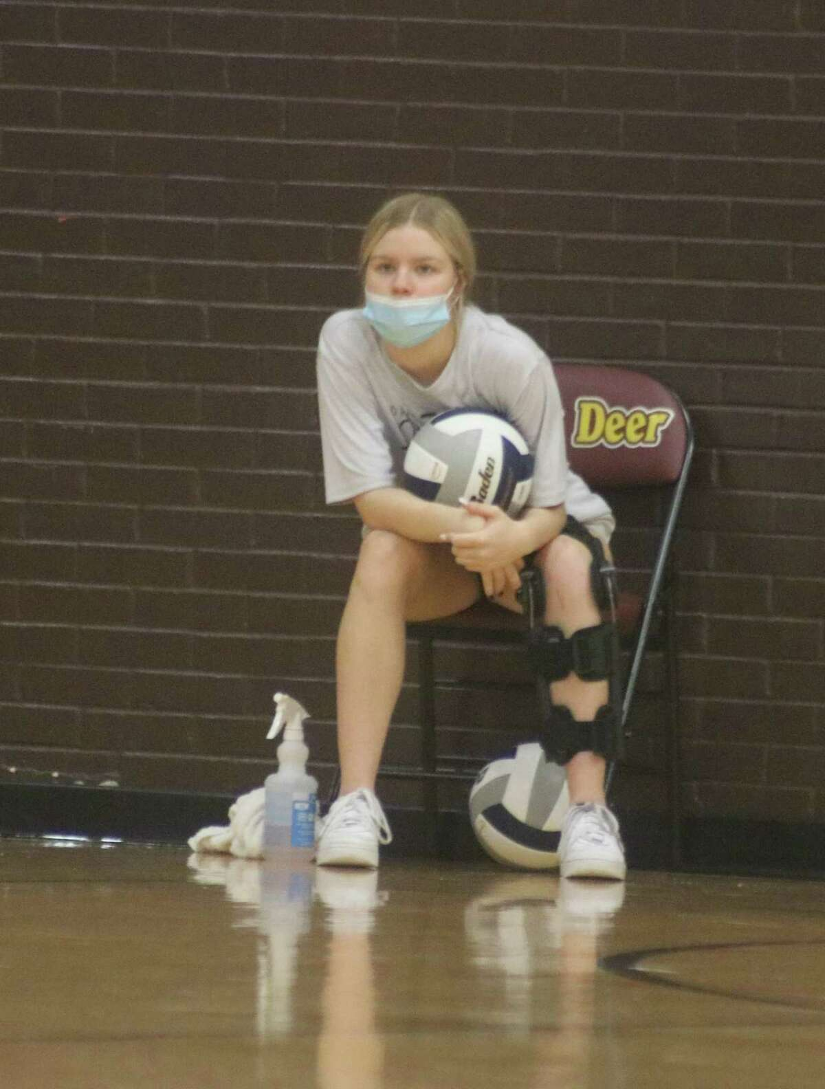 With disinfectant at the ready, Kayley Bowles has a couple of sanitized volleyballs she has rubbed down and ready to use during Tuesday night's match.