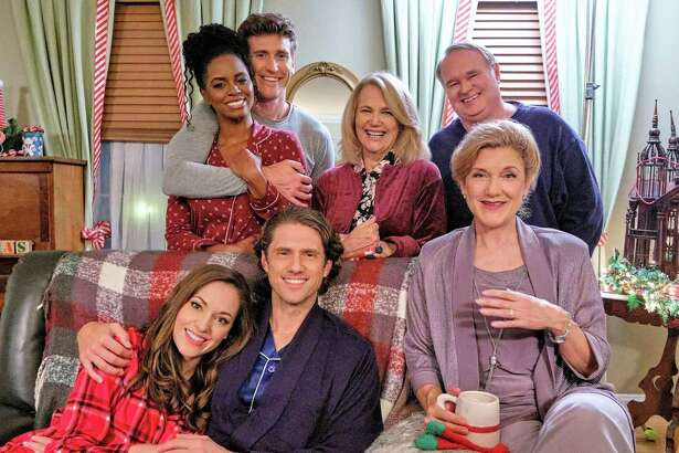 """In """"One Royal Holiday,"""" premiering Oct. 31 on Hallmark, Anna (Laura Osnes), far left on couch, offers a stranded mother and son (Aaron Tveit), middle on couch, shelter during a blizzard, and discovers they're royalty. Also pictured: Victoria Clark, Krystal Joy Brown, Bradley Rose, Geraldine Leer and Tom McGowan."""