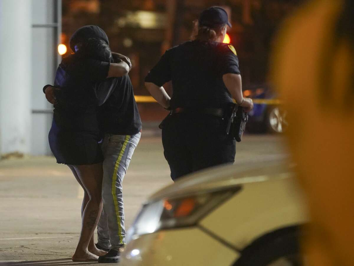 Onlookers comfort while Houston Police investigate a triple homicide at DD Sky Club in the 2100 block of Chenevert Street in Houston on Tuesday, Oct. 20, 2020. At least two shooters were involved in the incident during an open-mic night that left three people dead and one wounded.