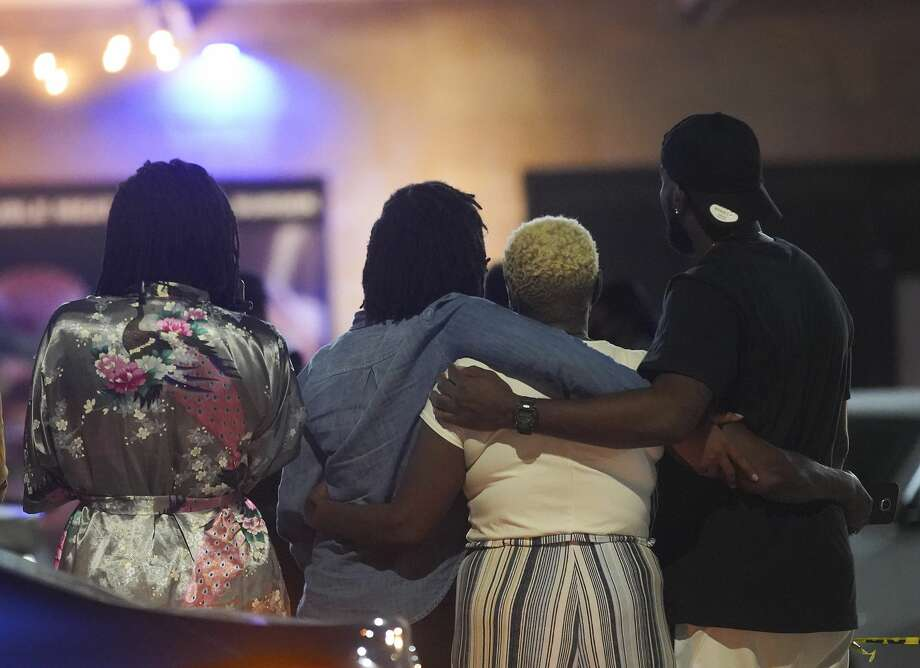 Onlookers comfort each other as they stand outside the police tape while Houston Police investigate a triple homicide at DD Sky Club in the 2100 block of Chenevert Street in Houston on Tuesday, Oct. 20, 2020. At least two shooters were involved in the incident during an open-mic night that left three people dead and one wounded. Photo: Elizabeth Conley/Staff Photographer / © 2020 Houston Chronicle