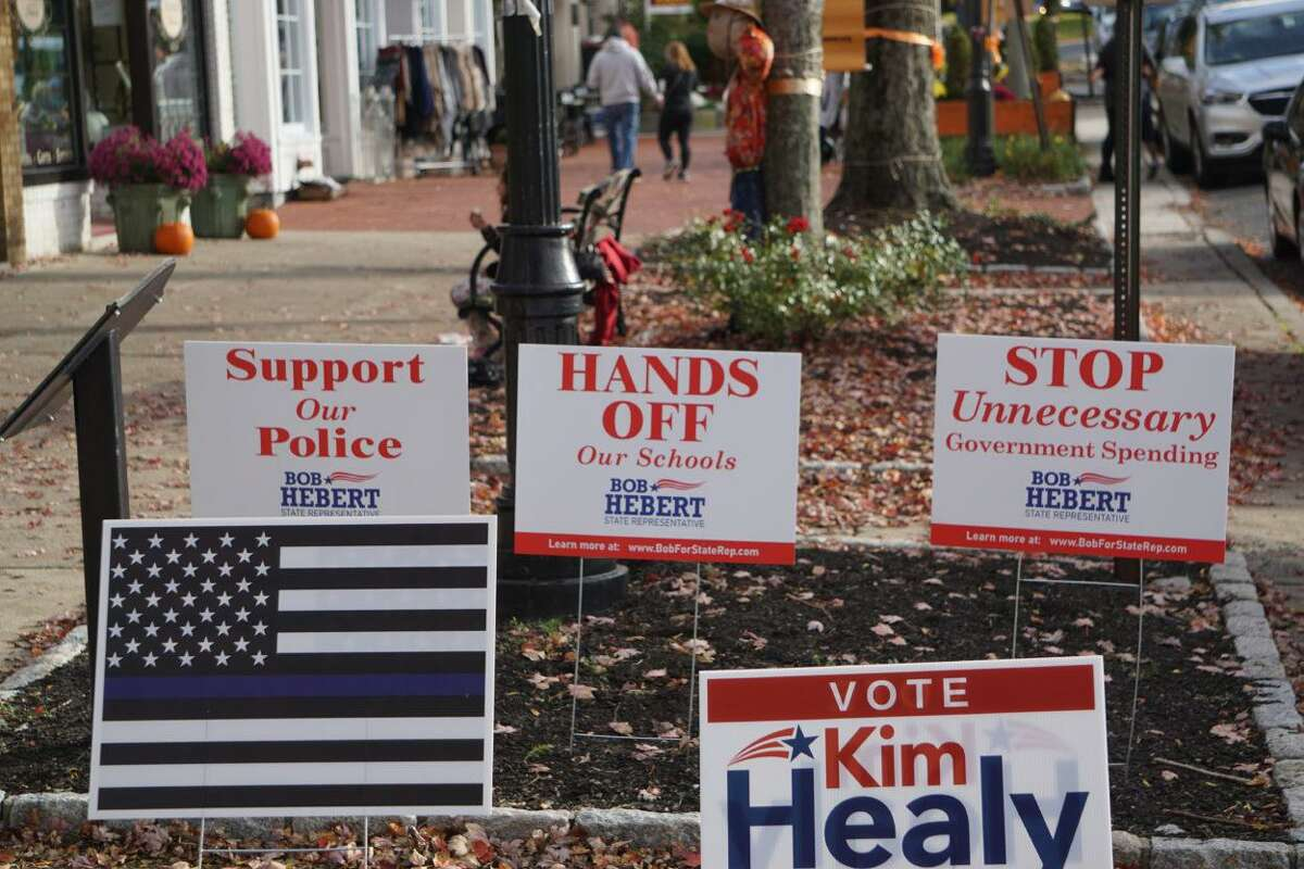 """Bob Hebert's lawn signs portray suburbs as threatened by school regionalization and police defunding. The """"thin blue line"""" flag supporting police is prominently featured at his headquarters."""