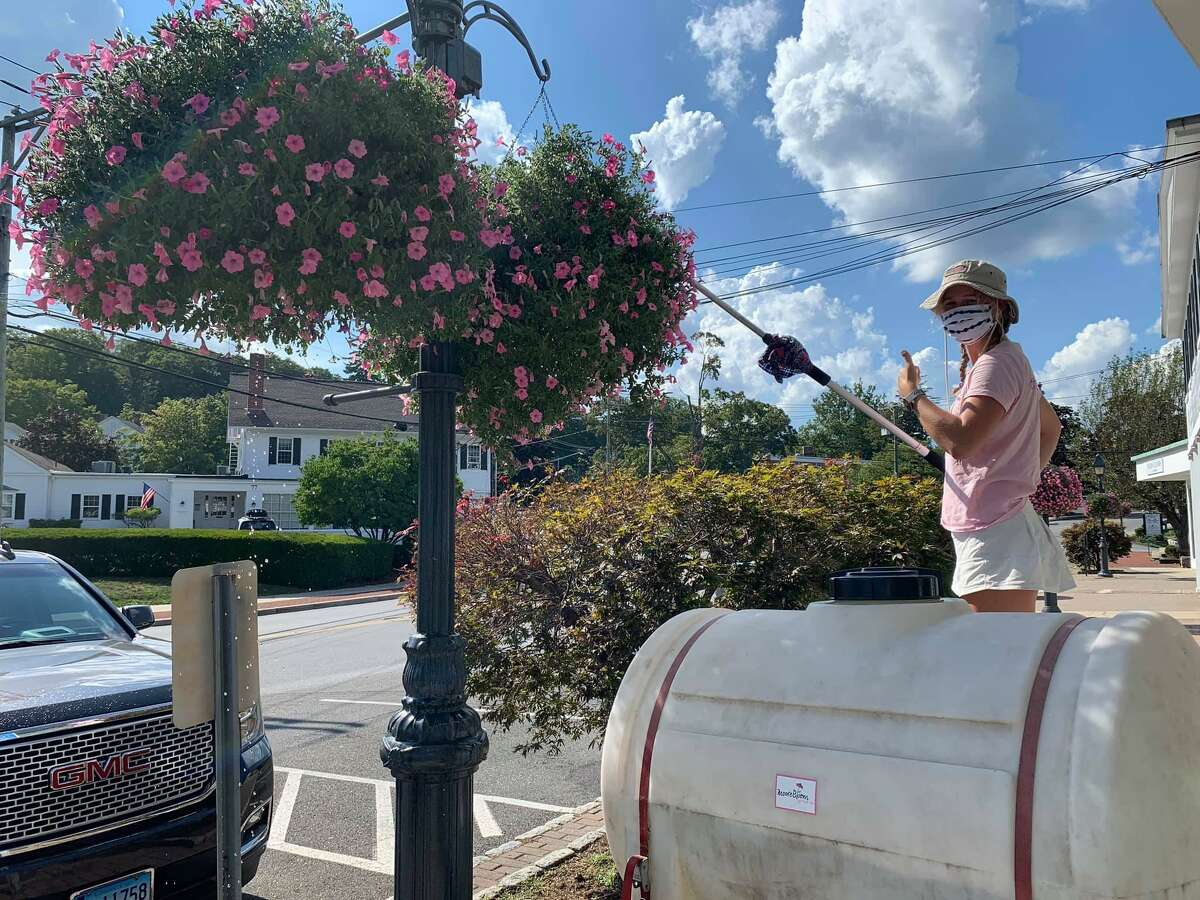 """Spencer Moore of Moore Blooms waters the flower baskets in Wilton Center over the summer. The """"Making Wilton Beautiful"""" campaign is raising money to purchase flower baskets for Wilton Center next year."""