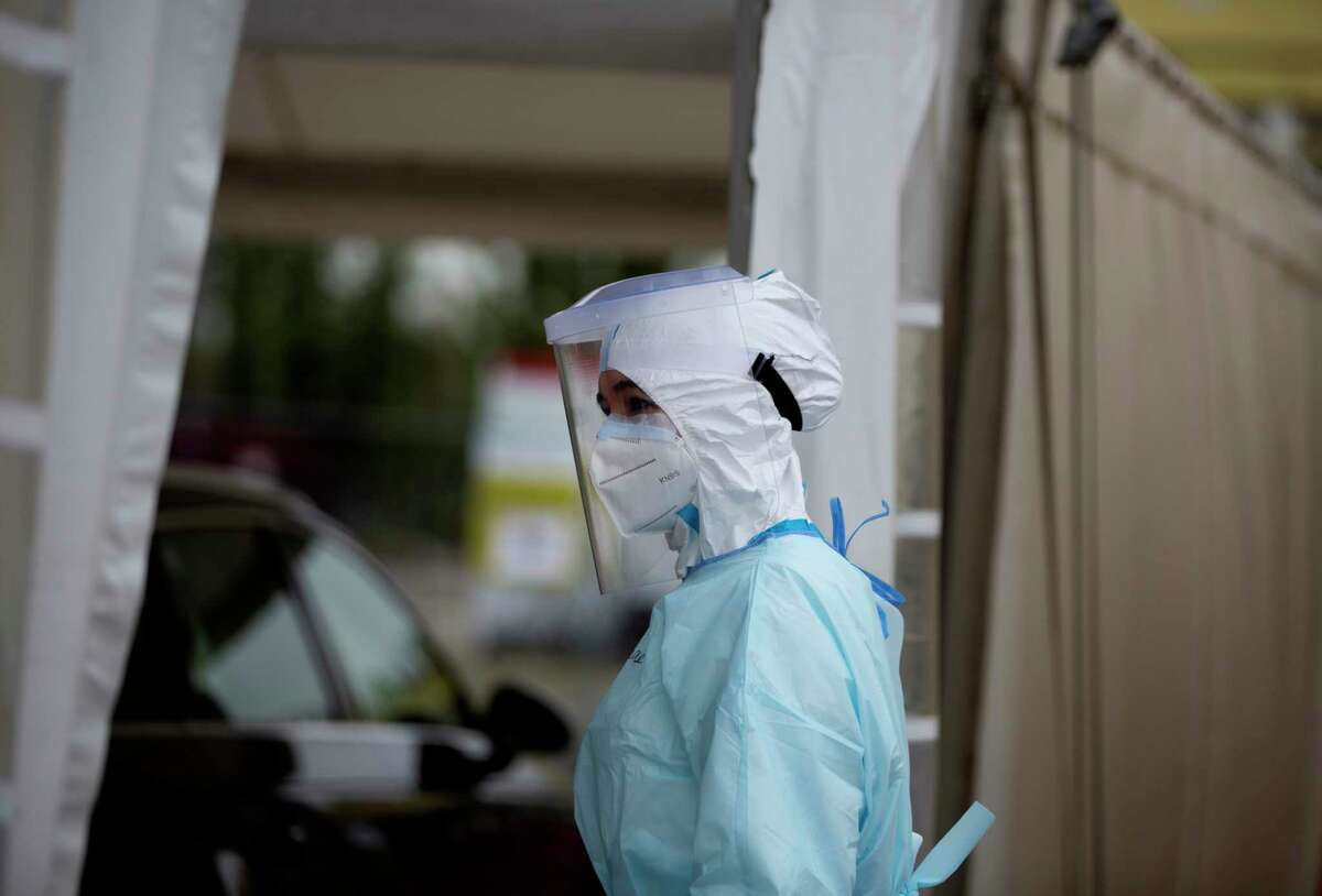 A health care worker waits for a car to stop in a tent for so she can administer a nose-swab test at the mobile COVID-19 testing site in Antwerp, Belgium, Tuesday, Oct. 20, 2020. Bars and restaurants across Belgium have been shut down for a month and a night-time curfew entered into force Monday, as health authorities warned of a possible sanitary