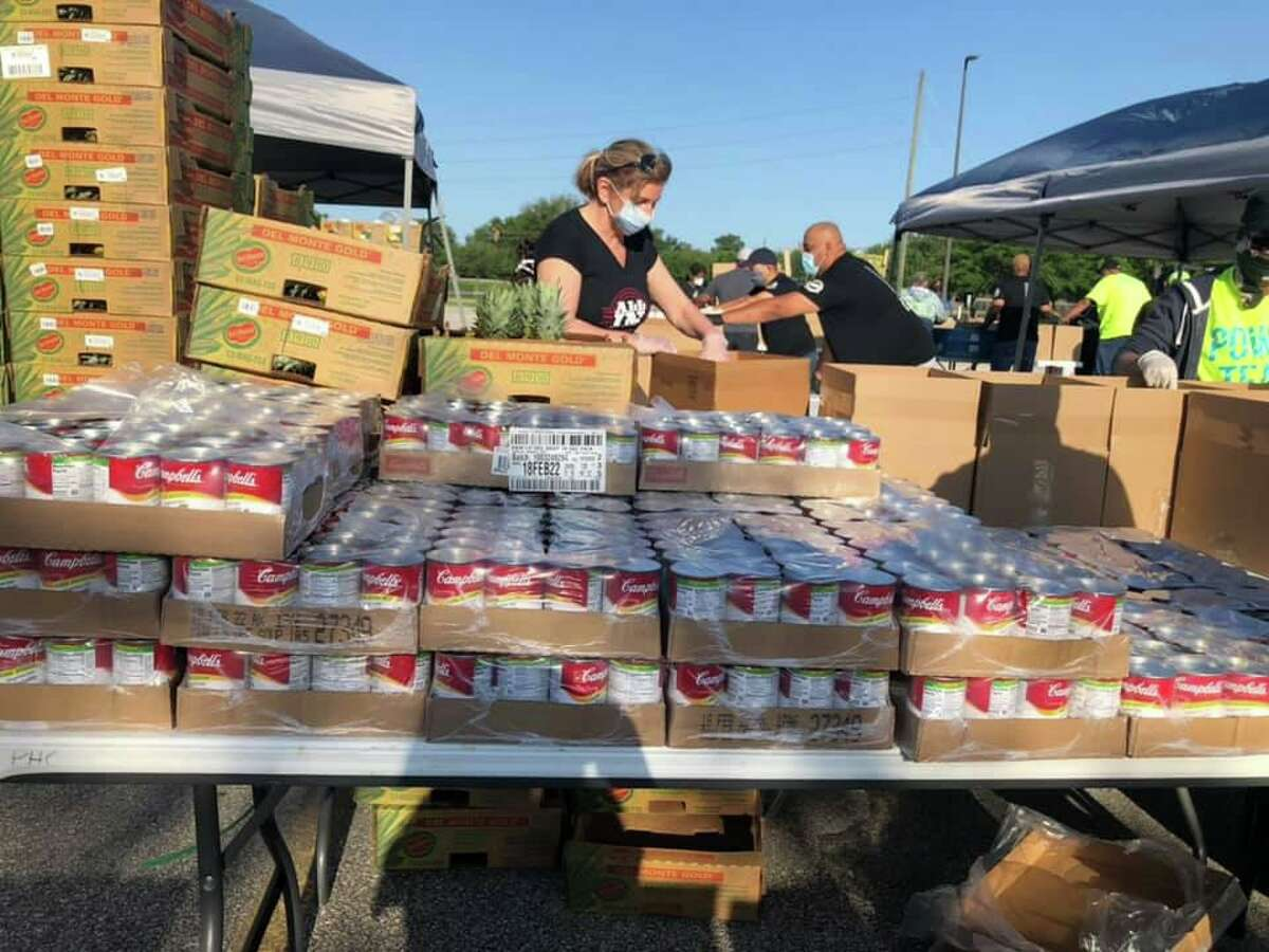 A Katy Christian Ministries volunteer helps distribute food to families on April 25, 2020.