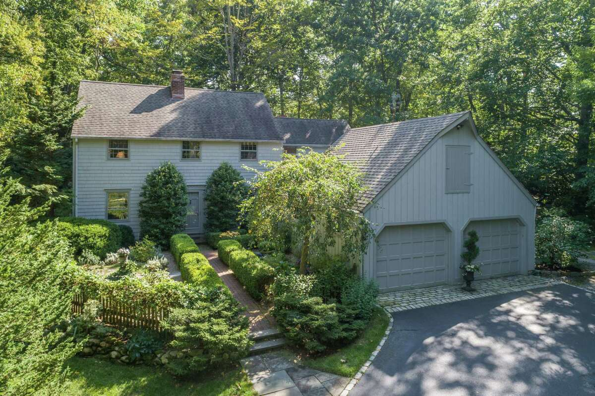 The gray colonial house at 9 Little Fox Lane in Lower Weston sits on a 2.03-acre level, sloping, wooded and attractively landscaped property.
