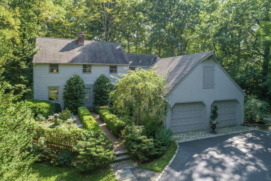 The gray colonial house at 9 Little Fox Lane in Lower Weston sits on a 2.03-acre level, sloping, wooded and attractively landscaped property. Photo: Contributed Photo /