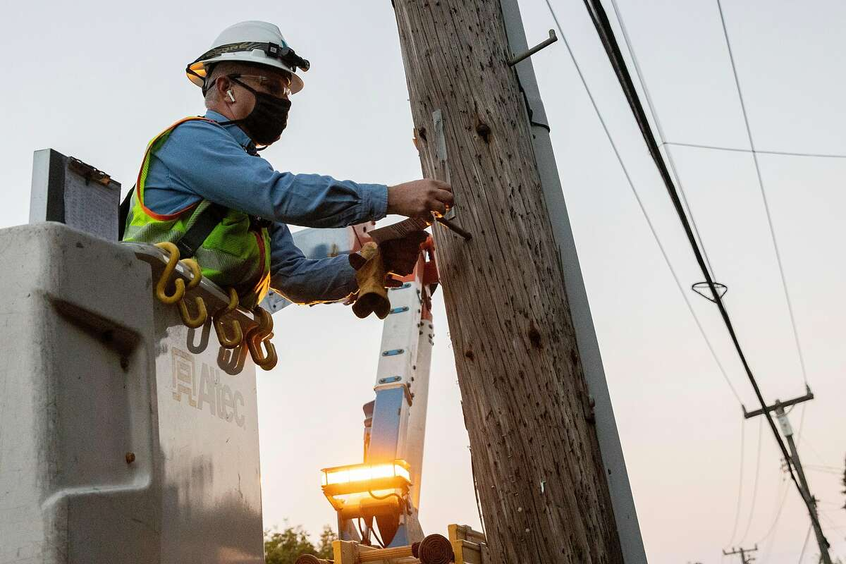 PG&E line inspector Tim Bauer tags a power line as cleared in the Montclair Village neighborhood of Oakland.