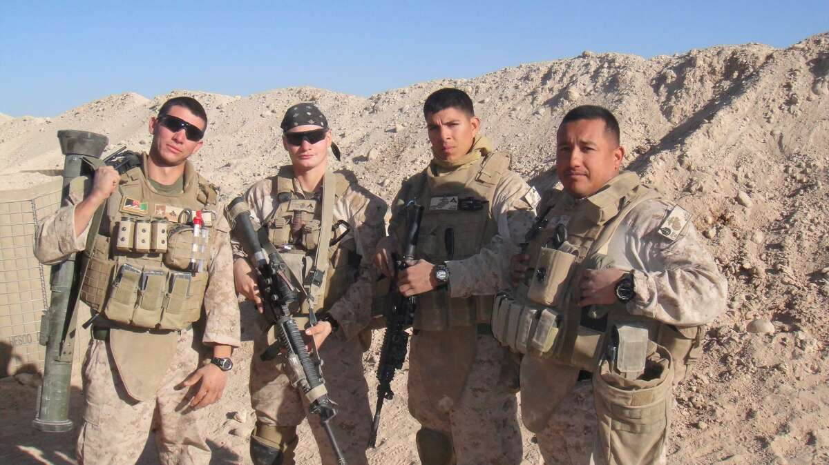 Dillonger Hackett, left, is seen while deployed overseas. He is suing his accusers after sexual assault charges against him were dropped this month.