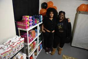 Community organizers Shalonda Faircloth, left, and Janelle Brandon, right, of Schenectady stand with goods they collected to give away through their 518 Free Store on Wednesday, Oct. 21, 2020, in Faircloth's basement in Schenectady, N.Y. The virtual online store offers free items, ranging from toothpaste to laundry detergent to diapers to needy people. They take orders on Mondays and make deliveries on Wednesday. (Will Waldron/Times Union)
