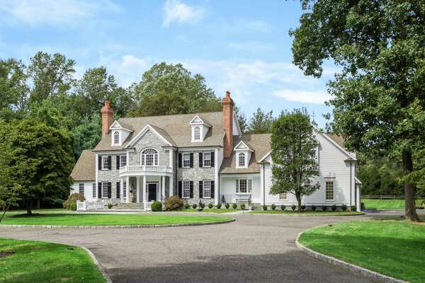 The stone and wood colonial house at 115 Senate Lane in Fairfield features 10,214 square feet of living space and is set on a level property of almost five acres.