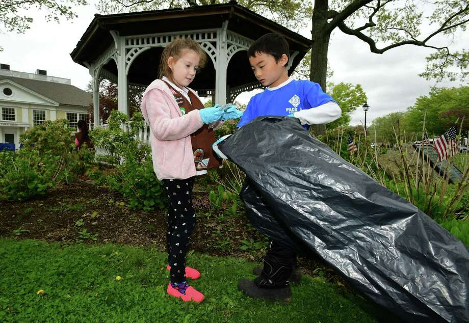 Brownie with Wilton Troop 50734, Ruth Frisbee and Cub Scout with Pack 22, Alex Shiue participate in Wilton's Townwide Cleanup last year. Cub Scouts participate in a number of community service events. Photo: Erik Trautmann / Hearst Connecticut Media / Norwalk Hour