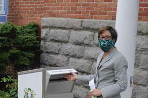 Town Clerk Wendy Lionetti shows off the ballot drop box on Bailey Avenue near a side entrance to town hall.
