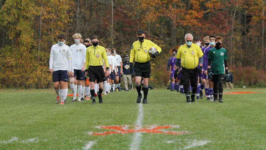 Calvary Baptist (right), Saginaw Valley Lutheran (left) and the referees walk down the middle of the Kings' field before a Division 4 district semifinal on Oct. 20. CBA won 4-2. Photo: Austin Chastain/Austin.Chastain@hearstnp.com