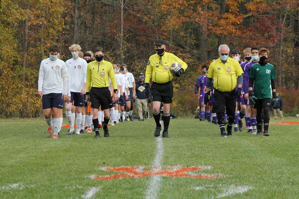 Calvary Baptist (right), Saginaw Valley Lutheran (left) and the referees walk down the middle of the Kings' field before a Division 4 district semifinal on Oct. 20. CBA won 4-2.