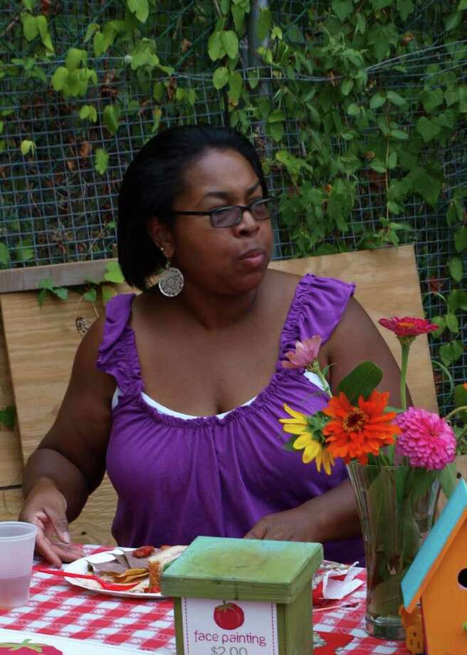 """Laura Murphy, a Housing Authority board member, resident of Armstrong Court, and member of the Armstrong Court Organizing Team acted as a face painting artist during the recent """"Music in the Garden"""" event. Photo: Contributed Photo / Greenwich Citizen"""