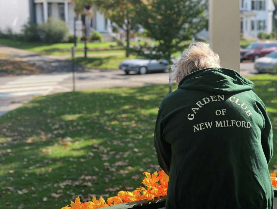 Kathy Elmore sports a garden club sweatshirt as she hangs fall garland around the bandstand. Photo: Deborah Rose /Hearst Connecticut Media / Danbury News Times