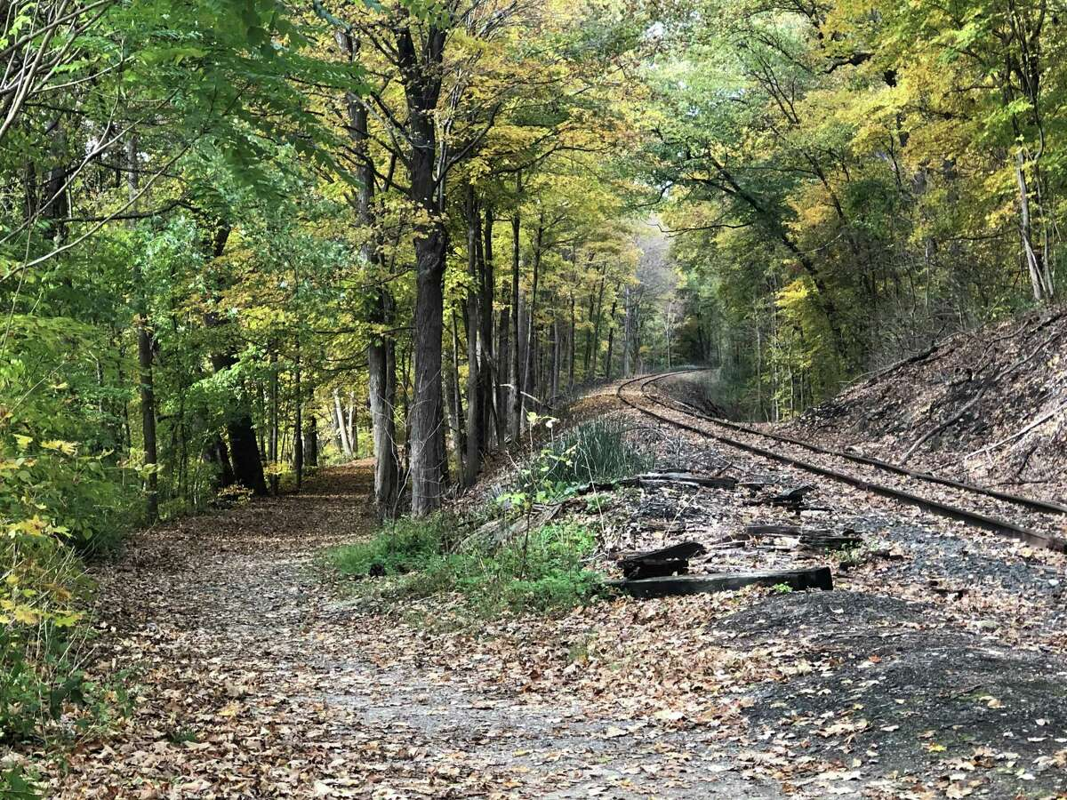 """The autumn foliage creates a picturesque scene along the railroad tracks and the path for Sega Meadows in New Milford on a recent afternoon. It's hard not to think of poet Robert Frost's words: """"Two roads diverged in a wood and I - I took the one less traveled by, and that has made all the difference."""""""