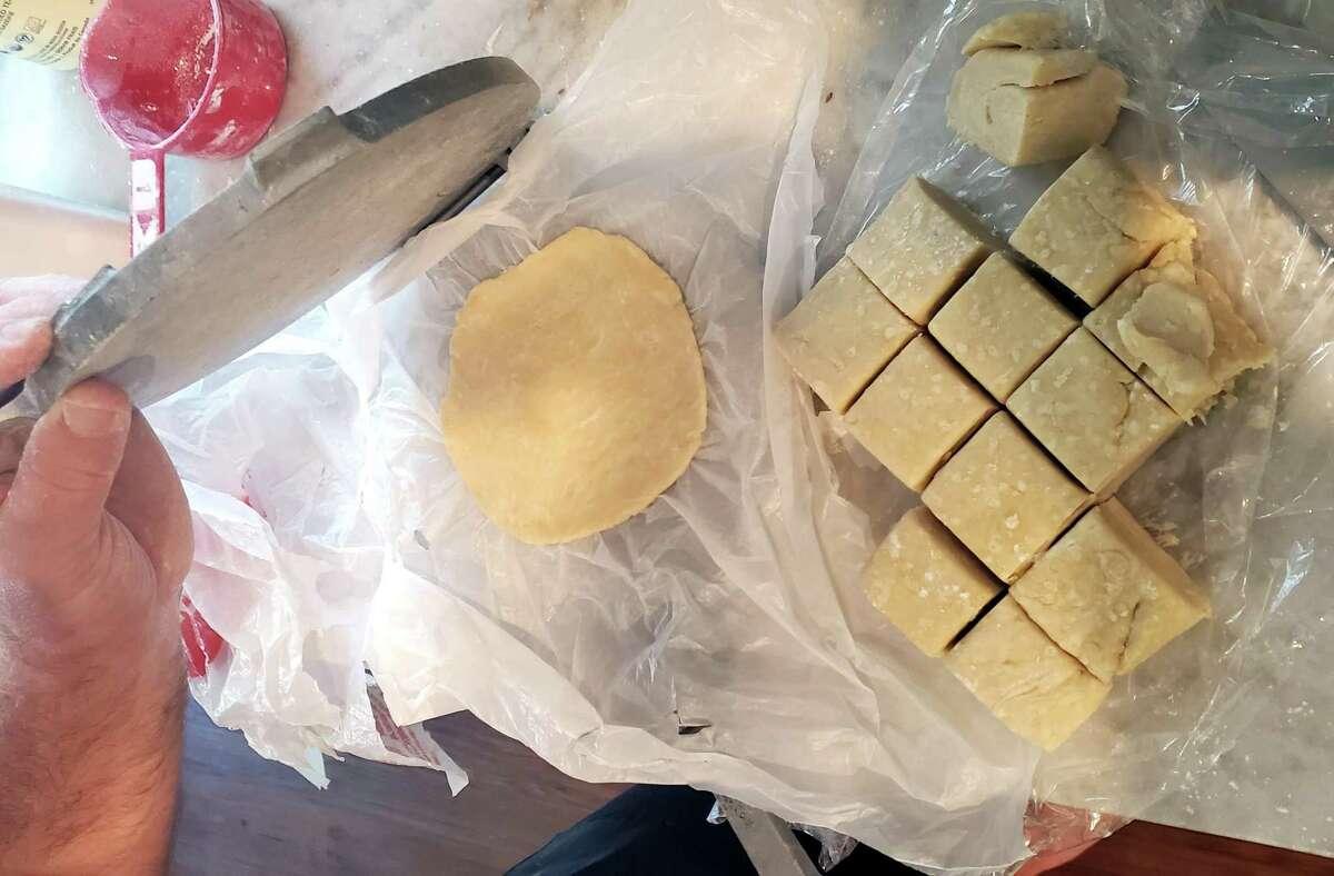 Empanada dough can be shaped into rounds using a tortilla press.