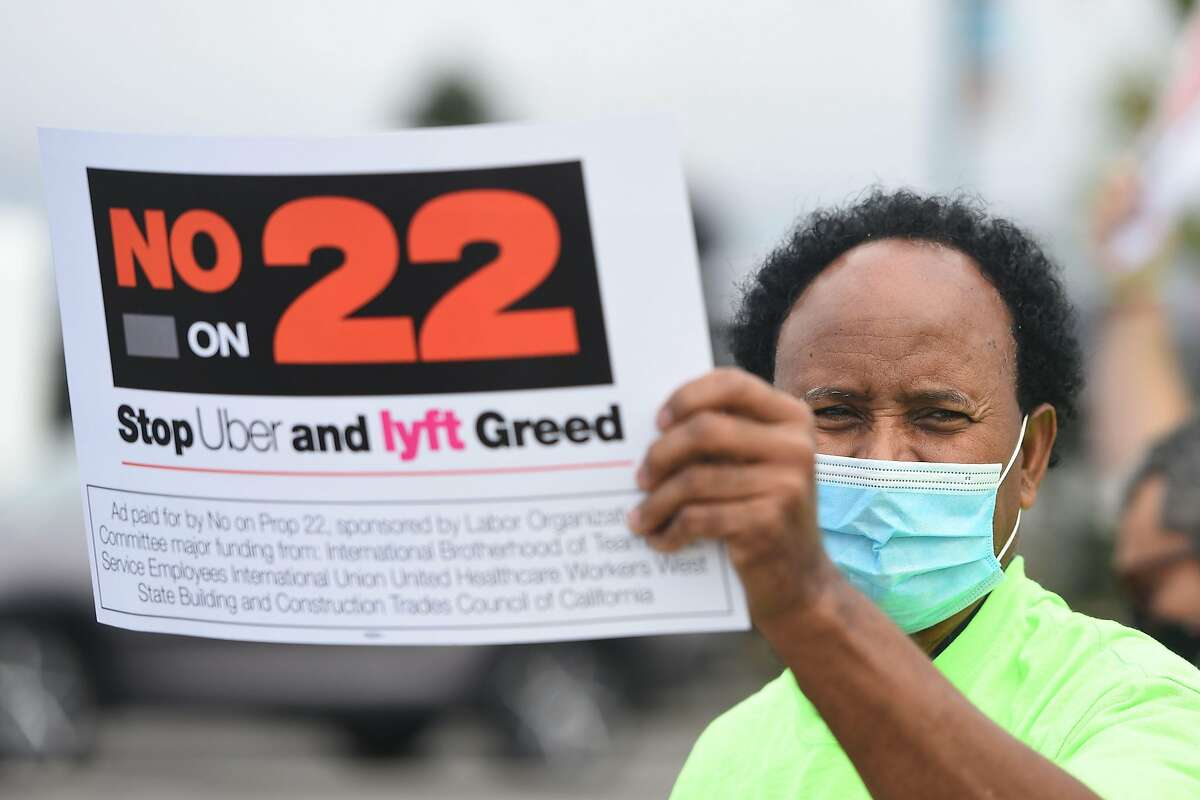 A rideshare driver holds up a sign supporting a