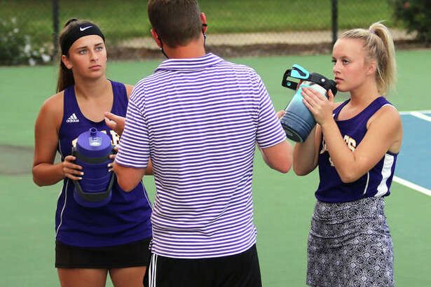 CM seniors Hannah Butkovich (left) and Kennedy Loewen (right) listens to instruction from Eagles coach Matt Carmody during their girls tennis doubles match against Jersey on Sept. 16 at Moore Park's Simpson Tennis Center in Alton. Butkovich and Loewen finished their prep career as two-time state qualifiers.