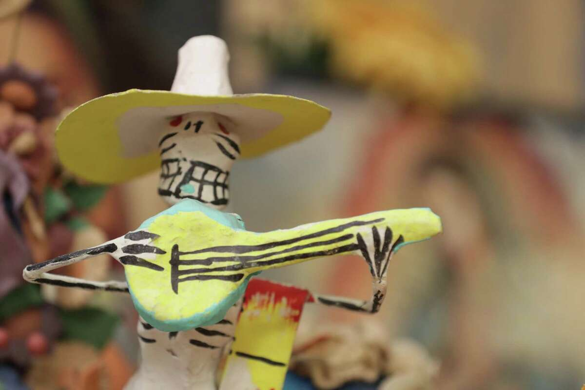Paper maches skeletons and miniature plastic or clay skeletons are used in Dia de Los Muertos (Day of the Dead) altars Saturday, Oct. 10, 2020, in Houston.