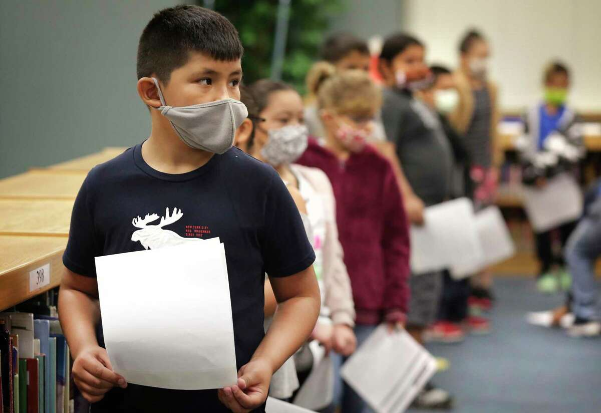 Technicians from Community Labs test staff and students at Barrera Veterans Elementary School in Somerset ISD for the coronavirus Wednesday. Matthew Gallegos, a third grader at the school, holds his permission slip in line with other students.