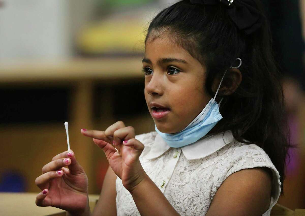 Technicians from Community Labs test staff and students at Barrera Veterans Elementary School in Somerset ISD for the coronavirus Wednesday. Arlin Macias, a first grader at the school, asks for directions on how to test herself.