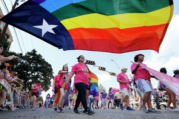 People marching with the Mobilize for Equality group pass by the Texas rainbow flag during the Texas Freedom Parade, Sunday, September 17, 2017. (Tom Fox/The Dallas Morning News/TNS)