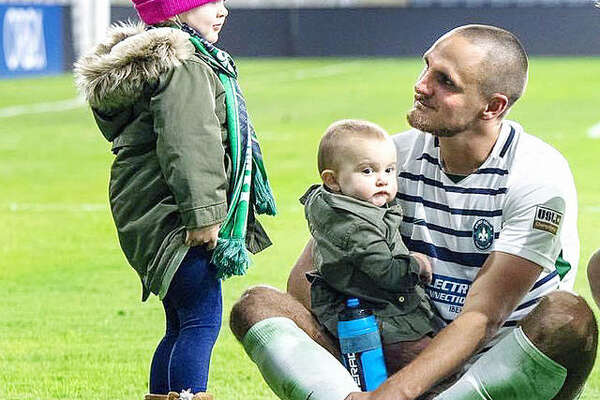 Sam Fink visits with daughters Evelyn, left, and Eleanor on the pitch Saturday night at Lynn Family Stadium in Louisville, Ky. Fink's STLFC soccer team lost its USL playoff game to Louisville City 2-0, ending a six-year run in St. Louis. The team is ceasing operations to make way for the Major League Soccer expansion St. Louis City SC team, which will begin playing in 2023.