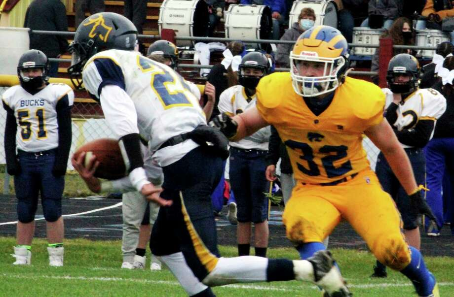 Evart's Cole Hopkins (32) looks to make a play against the Roscommon ball-carrier in Saturday's homecoming football game. (Pioneer photo/John Raffel)