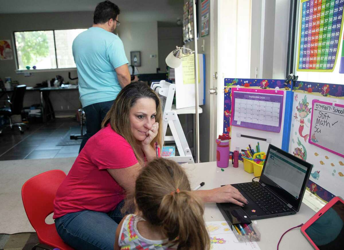Flight attendant Jessica Trujillo helps her daughter, Aris, 5, while her husband, Rene Trujillo, also a flight attendant, helps their son, Micah, 8, work on virtual schooling Thursday, Oct. 1, 2020, in Houston.