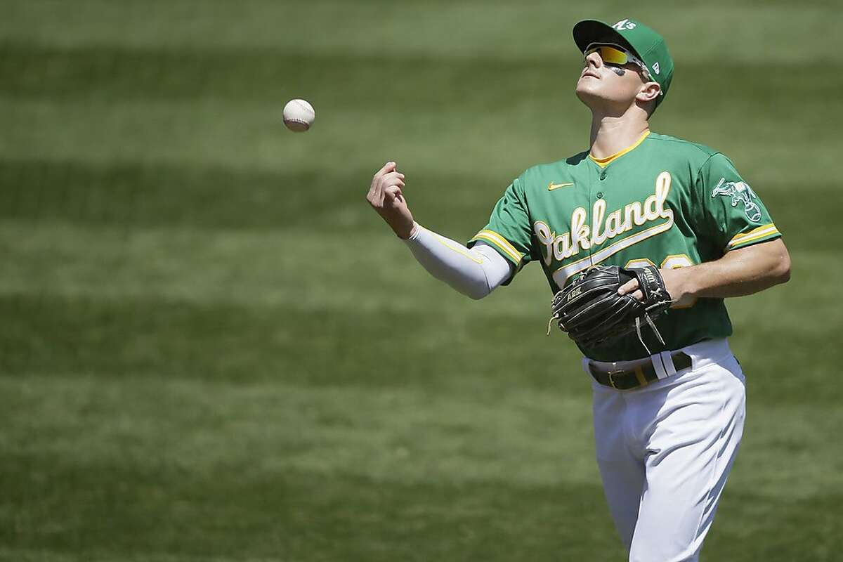Oakland Athletics third baseman Matt Chapman (26) throws the ball into the empty stands after the end of the second inning in an MLB game against the Houston Astros at RingCentral Coliseum on Saturday, Aug. 8, 2020, in Oakland, Calif.