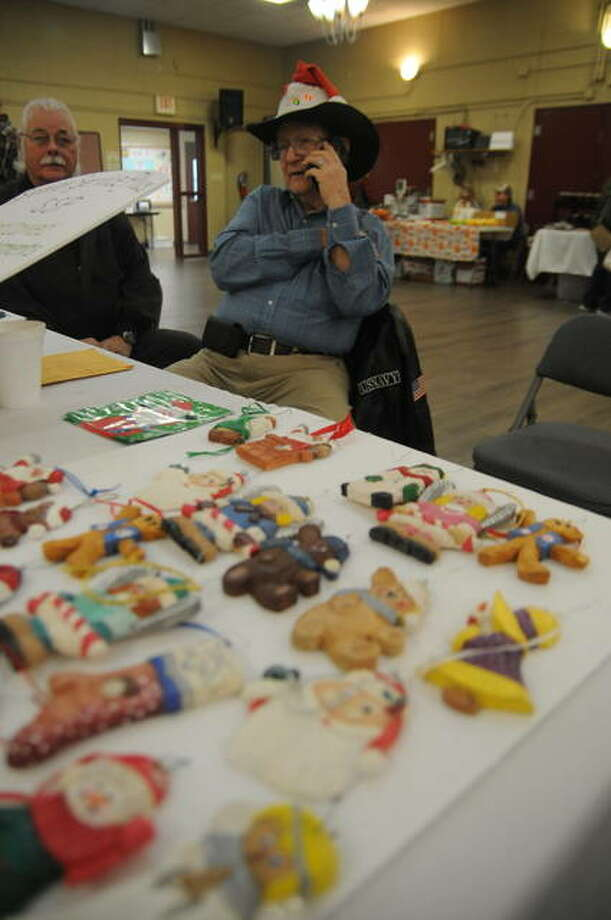 In this file photo from 2019, Vernon Langer of Godfrey staffs the Senior Services Plus booth, selling handcrafted wooden ornaments, during a Winter Market. The monthly events are set to resume Dec. 5.