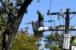 Work crews clear fallen tree limbs from utility lines along Hawthorne Avenue on Thursday, Oct. 8, 2020, in Delmar, N.Y. Strong winds from a fast moving storm on Wednesday evening took down trees caused damage throughout the Capital Region.