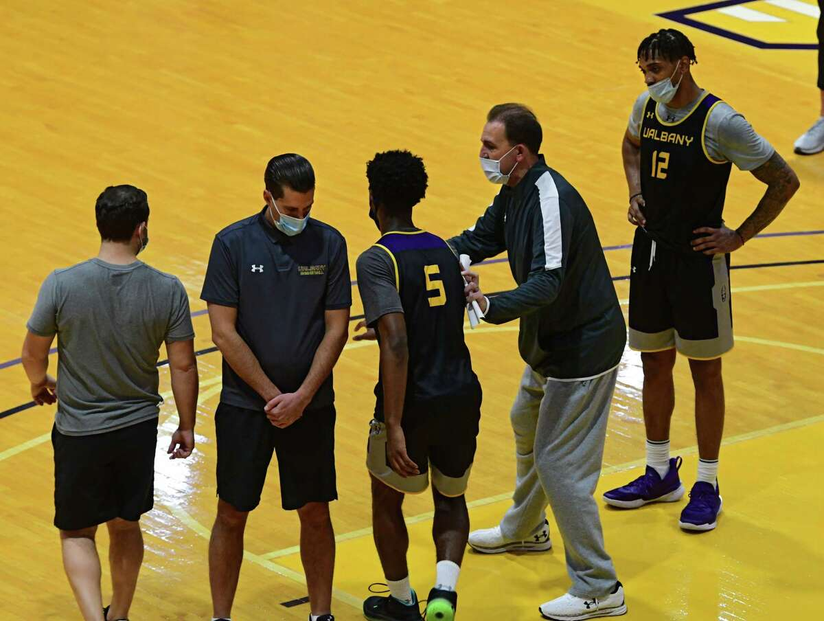 Head Coach Will Brown, second from right, talks to his players as the University at Albany men's basketball team practices in the SEFCU arena on Wednesday, Oct. 21, 2020 in Albany, N.Y. (Lori Van Buren/Times Union)