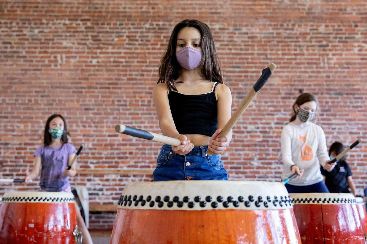 Students wear masks while participating in a Taiko drumming class as part of an arts pod organized by Dance Mission Theater in the Mission District of San Francisco, Calif. Tuesday, October 13, 2020. Several arts pods have popped up in San Francisco, funded by foundations for low-income kids since COVID-19 pandemic has shut down regular in-person schooling.