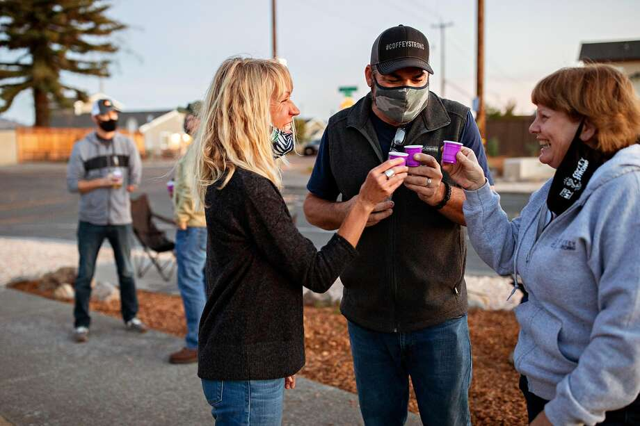 Sasha Butler, Steve Rahmn and Anne Barbour do a little toast at Coffey Park in Santa Rosa on Oct. 9 when residents gathered for an evening of community and observance of the Tubbs Fire that destroyed the neighborhood in October 2017. Homes there continue to be rebuilt. Photo: Santiago Mejia / The Chronicle