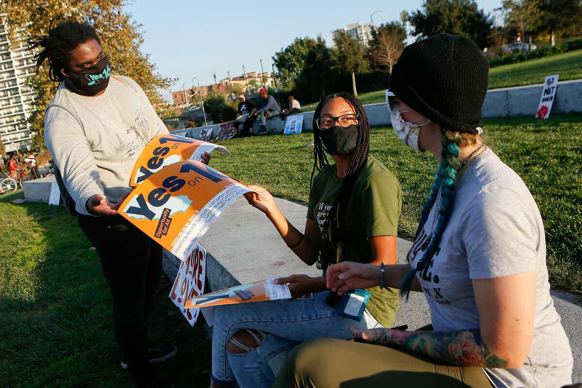 Spencer Staggers-Elmore hands out Yes on 16 signs to Kaylyn Goode (middle) and Amy Prindle at Lake Merritt on Friday.