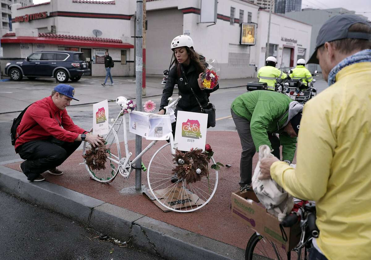Stefania Siragusa and Taylor Ahlgren place flowers on a Ghost Bike at South Van Ness Avenue and Howard Street during the Ride of Silence honoring killed cyclists in San Francisco, Calif., on Wednesday, May 15, 2019.